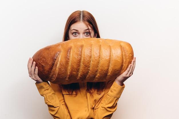 Gelukkige vrouw met een brood in de hand een brood in een horizontale positie op een lichte achtergrond