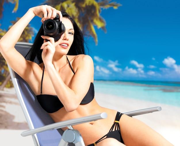 Gelukkige vrouw met een digitale camera die foto's op het strand neemt