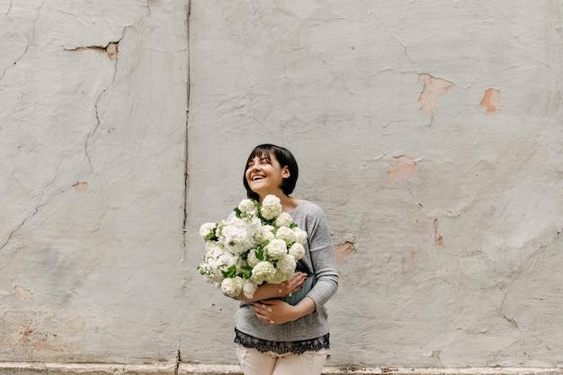 Gelukkige vrouw met een emmer met seizoensgebonden witte bloemen