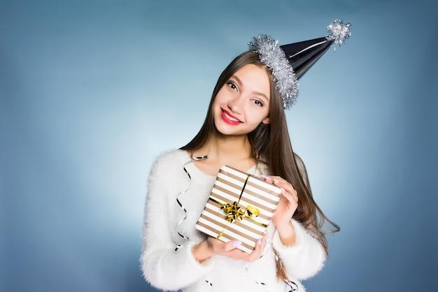 Gelukkige vrouw met een feestelijke hoed houdt een geschenk in haar handen