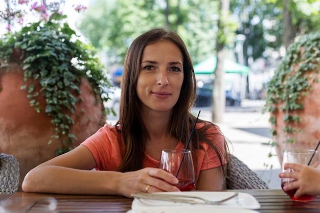 Gelukkige vrouw met een glas rood sap op een zomerterras van cafetaria.