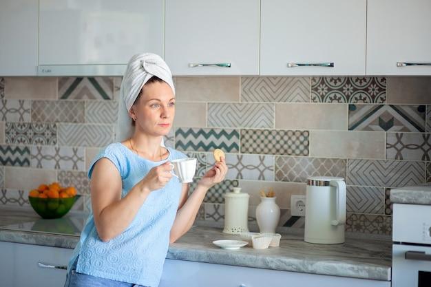 Gelukkige vrouw met een handdoek op haar drinkt koffie