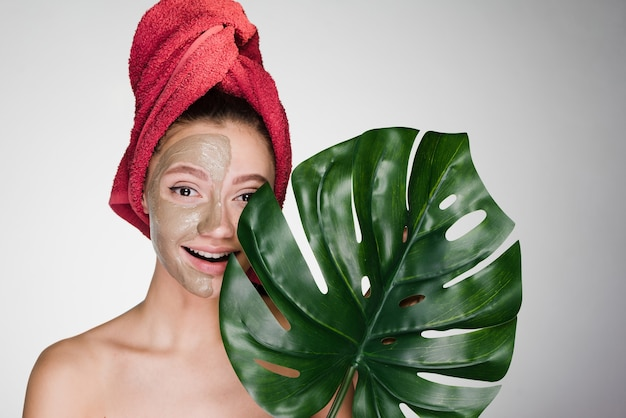 Gelukkige vrouw met een handdoek op haar hoofd brengt een reinigingsmasker op het gezicht aan en houdt een groot blad vast