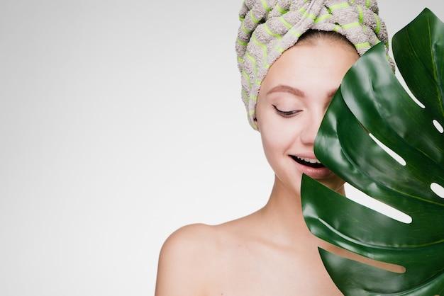 Gelukkige vrouw met een handdoek op haar hoofd houdt een groot blad vast