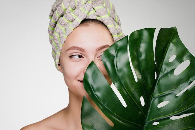 Gelukkige vrouw met een handdoek op haar hoofd na een douche houdt een groen blad vast