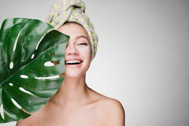 Gelukkige vrouw met een handdoek op haar hoofd nadat de douche pleisters onder de ogen heeft gezet