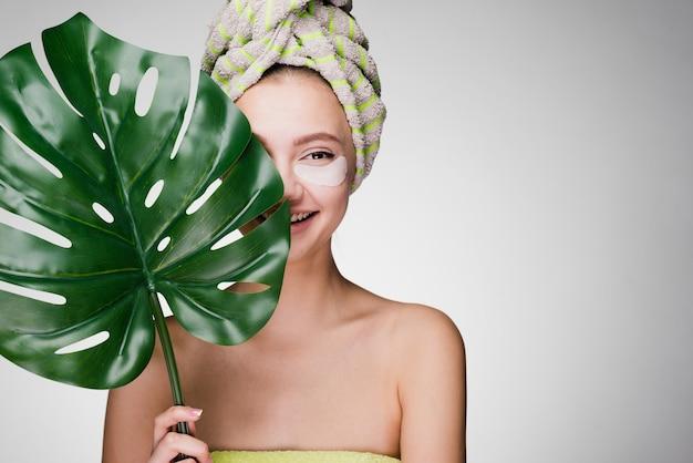 Gelukkige vrouw met een handdoek op haar hoofd sloeg vlekken onder de ogen