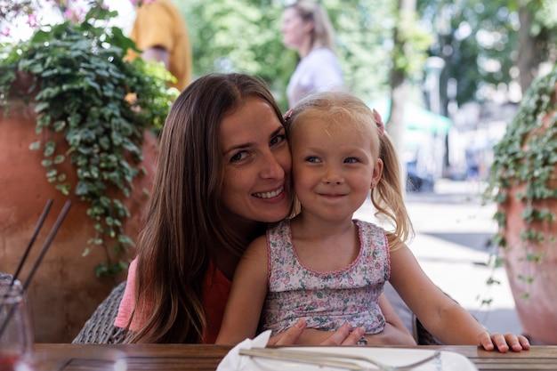 Gelukkige vrouw met een klein meisje op een zomerterras van cafetaria.