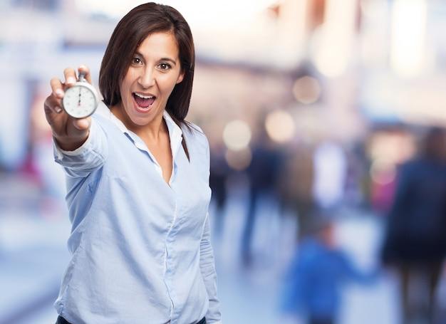 Gelukkige vrouw met een klok in haar hand