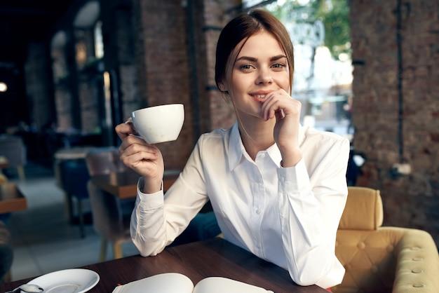 Gelukkige vrouw met een kopje in de hand zit in een stoel in het restaurant en het interieur