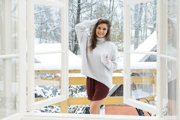 Gelukkige vrouw met een kopje warme drank op het balkon op winterdag