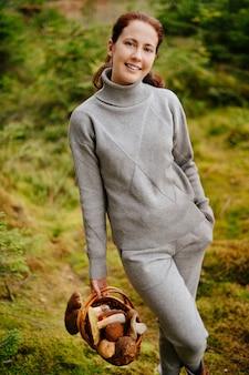 Gelukkige vrouw met een mand met eetbare paddenstoelen in het bos het oogstseizoen