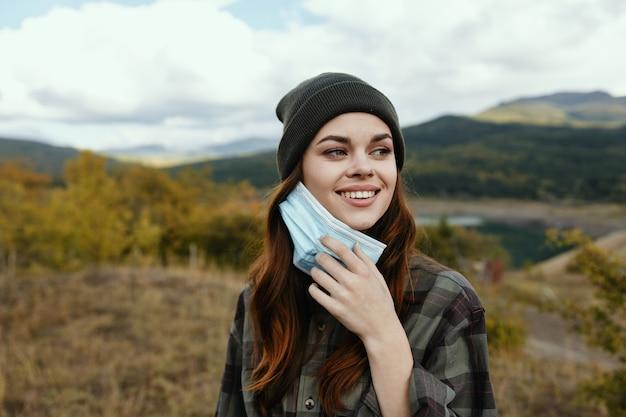 Gelukkige vrouw met een medisch masker in haar hand op aard in het bos.