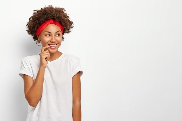 Gelukkige vrouw met een mooie uitstraling, kijkt graag opzij, draagt een hoofdband en een casual t-shirt, heeft perfecte, gelijkmatige tanden