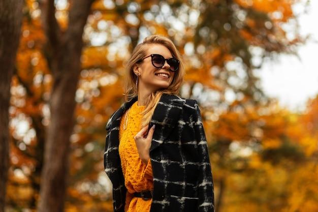 Gelukkige vrouw met een schattige glimlach met tanden in modieuze herfstkleren met een gebreide trui en een jas in de natuur op de achtergrond van een boom met geel herfstblad. glimlachend vrouwelijk mooi gezicht