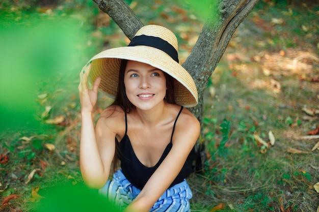 Gelukkige vrouw met een vrolijke brede glimlach zit in een park onder een boom in een zomer thaise kegel hoed in de frisse lucht.