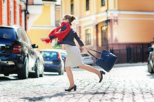 Gelukkige vrouw met een zak steekt de straat over
