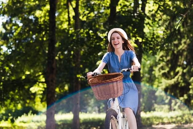 Gelukkige vrouw met fiets in bos