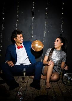 Gelukkige vrouw met fles die dichtbij de mens met ballon dichtbij glazen glimlacht