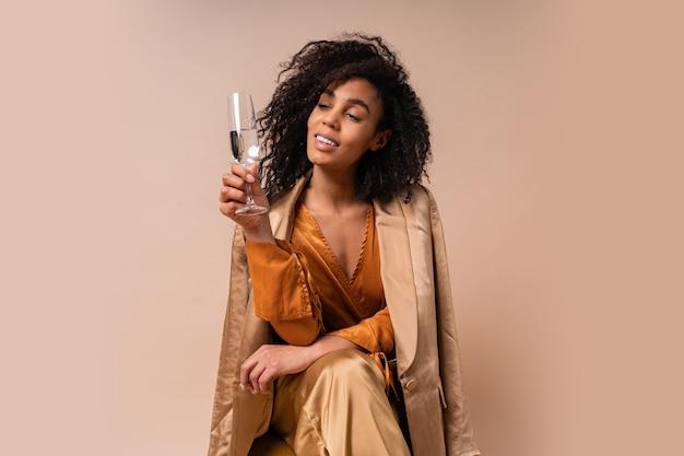 Gelukkige vrouw met gebruinde huid met perfect krullende haren met glas wijn, ielegant oranje blouse en zijden broek zittend op vintage stoel beige muur.