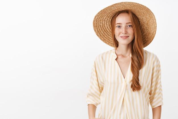Gelukkige vrouw met gember haar en sproeten in trendy strooien hoed en gele blouse glimlachend teder en vrouwelijk fotograferen van het oude europa