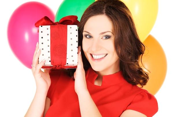 Gelukkige vrouw met geschenkdoos en ballonnen