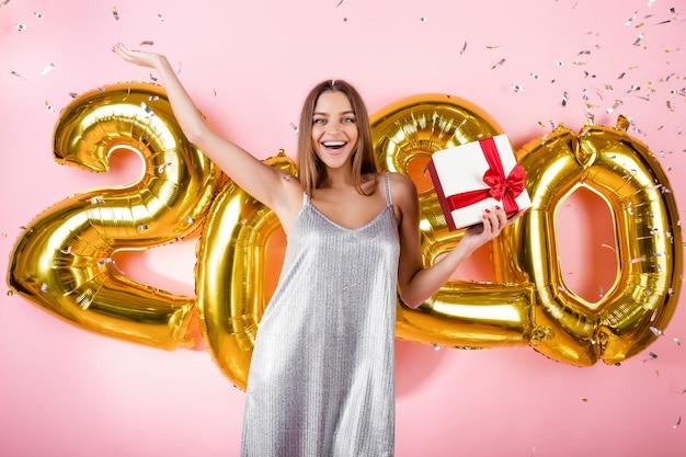 Gelukkige vrouw met geschenkdoos en zilveren confetti en gouden 2020 nieuwe jaar ballonnen geïsoleerd over roze