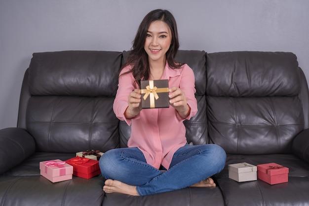 Gelukkige vrouw met geschenkdoos in de woonkamer