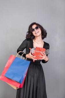 Gelukkige vrouw met geschenkdozen en boodschappentassen