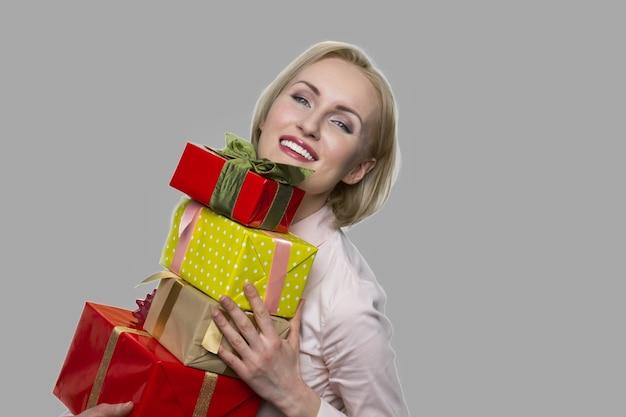 Gelukkige vrouw met giftdozen op grijze achtergrond. mooie glimlachende vrouw ontving veel cadeaus voor verjaardag. eindejaarsuitkering.