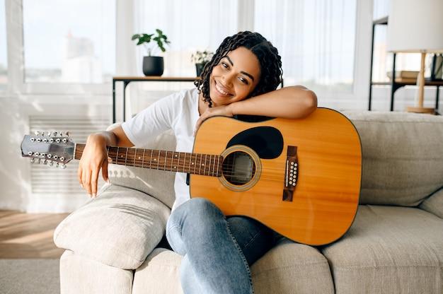 Gelukkige vrouw met gitaar zittend op de bank thuis. mooie dame in oortelefoons ontspannen in de kamer, vrouwelijke geluidsminnaar rusten