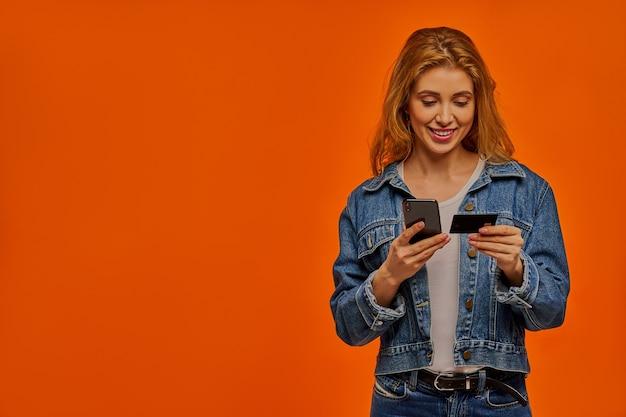 Gelukkige vrouw met golvend haar in een spijkerjasje houdt een telefoon vast en kijkt op een zwarte creditcard