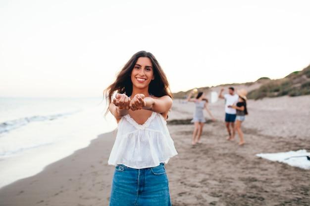 Gelukkige vrouw met haar vrienden op het strand
