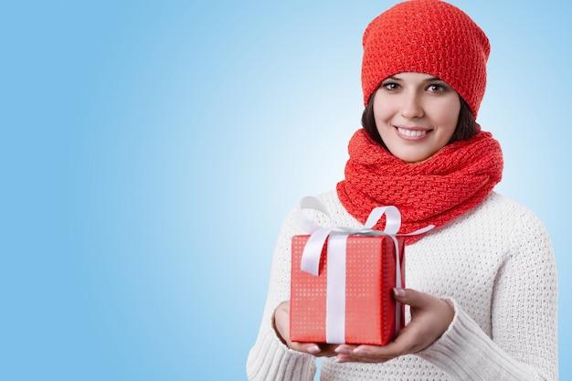 Gelukkige vrouw met heldere bruine ogen, donker haar, charmante glimlach die rode sjaal draagt, hoed en een heden in haar hand houdt