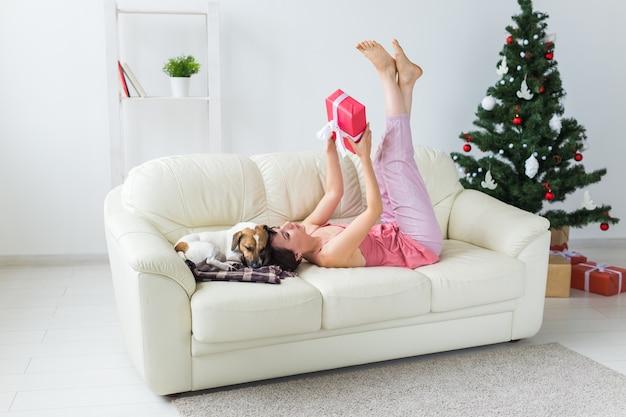 Gelukkige vrouw met hond en kerstboom met cadeautjes eronder