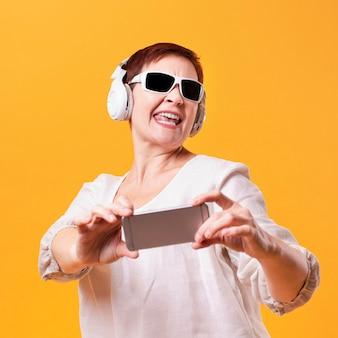 Gelukkige vrouw met hoofdtelefoons en telefoonmodel