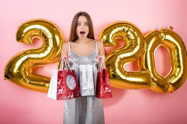 Gelukkige vrouw met kerstmis het winkelen giftzakken met gouden die ballons 2020 over roze worden geïsoleerd
