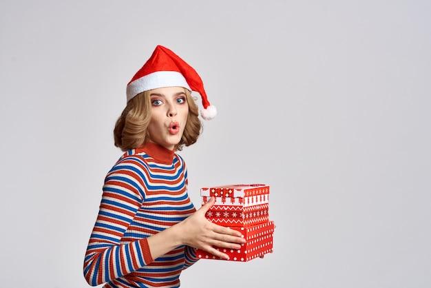 Gelukkige vrouw met kerstmisgiften in handen en rode hoed op hoofd nieuwjaarsvakantie bijgesneden weergave.