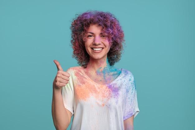 Gelukkige vrouw met kleurrijk holi-poeder dat duim toont