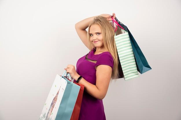 Gelukkige vrouw met kleurrijke boodschappentassen.