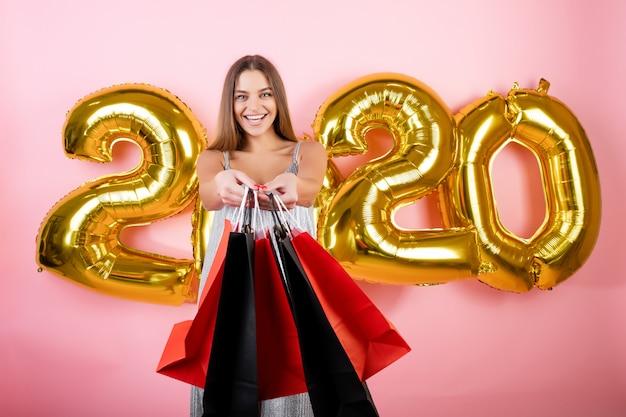 Gelukkige vrouw met kleurrijke die het winkelen zakken met kerstmisballons van 2020 over roze worden geïsoleerd