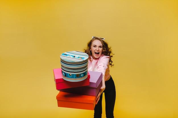 Gelukkige vrouw met kleurrijke kartonnen dozen na het winkelen op geel