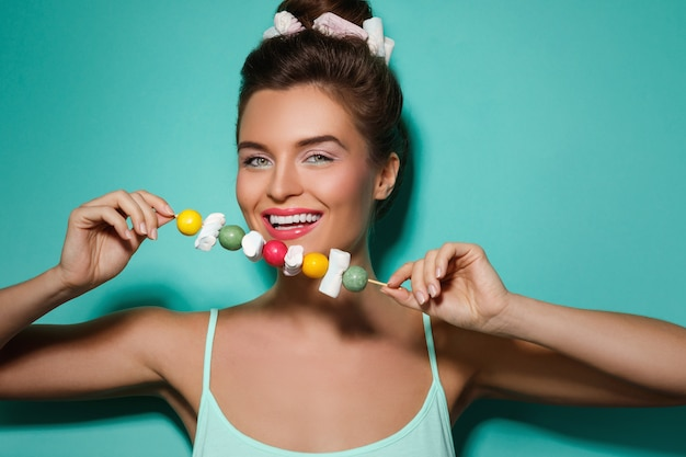 Gelukkige vrouw met kleurrijke make-up en zoet suikergoed op vleespen