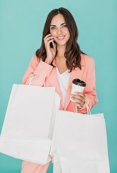 Gelukkige vrouw met koffie die bij smartphone spreekt
