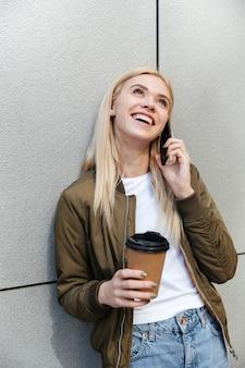 Gelukkige vrouw met koffie praten op smartphone