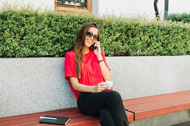 Gelukkige vrouw met kop koffie die op smartphone spreken