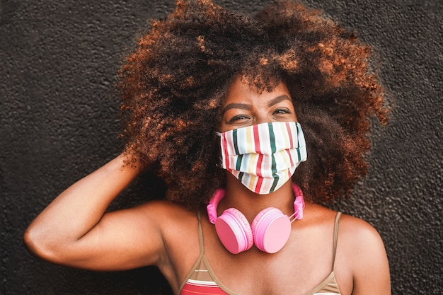 Gelukkige vrouw met koptelefoon die gezichtsmasker draagt tijdens de uitbraak van het coronavirus