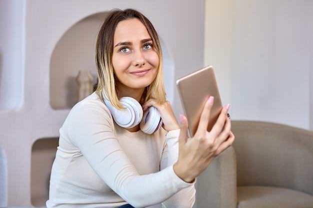 Gelukkige vrouw met koptelefoon maakt videogesprek in woonkamer
