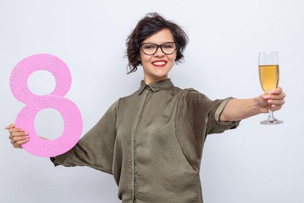 Gelukkige vrouw met kort haar met nummer acht gemaakt van karton en een glas champagne glimlachend vrolijk vieren internationale vrouwendag 8 maart