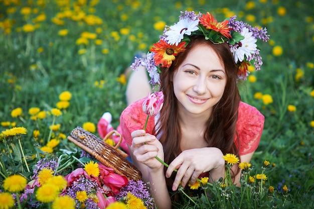 Gelukkige vrouw met kroon die op een weide met een boeket van bloemen ligt